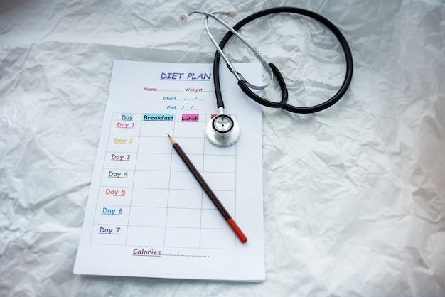 Het dieetplanningsplan zet naast pen en stethoscoop