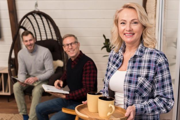 Het dienblad van de moederholding van koppen die met familie op de achtergrond stellen