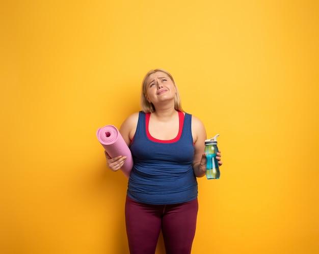 Het dikke meisje doet thuis gymnastiek. vermoeide uitdrukking