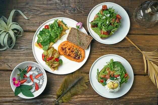 Het diner werd geserveerd met verschillende gerechten - hummus met omelet, avocadotoosts en yoghurt met chiazaad op een houten tafel. bovenaanzicht