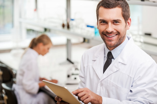 Het documenteren van het resultaat van experimenten. glimlachende jonge mannelijke wetenschapper die digitale tablet vasthoudt en naar de camera kijkt terwijl zijn vrouwelijke collega op de achtergrond werkt Premium Foto