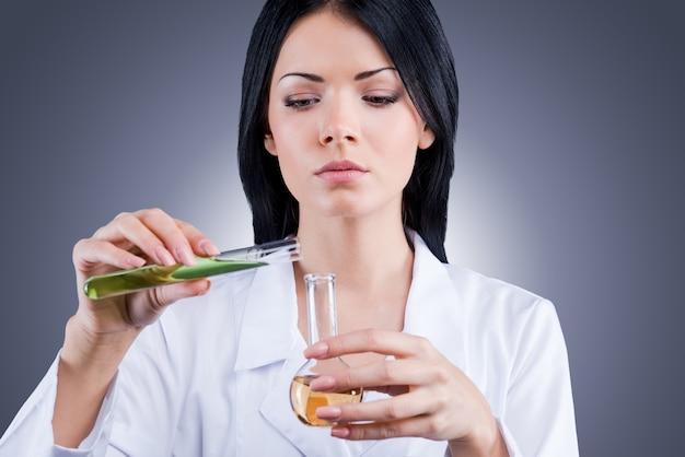 Het doel is om de remedie voor deze ziekte te vinden. vrouwelijke arts in wit uniform die kolven vasthoudt terwijl ze tegen een grijze achtergrond staat
