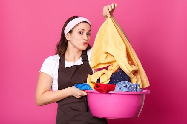 Het donkerbruine emotionele model stelt geïsoleerd over helderroze muur die zich met bassin vol kleurrijke vuile kledingstukken bevindt, die lichtgeel overhemd zorgvuldig met walging houdt. huishoudelijk concept.