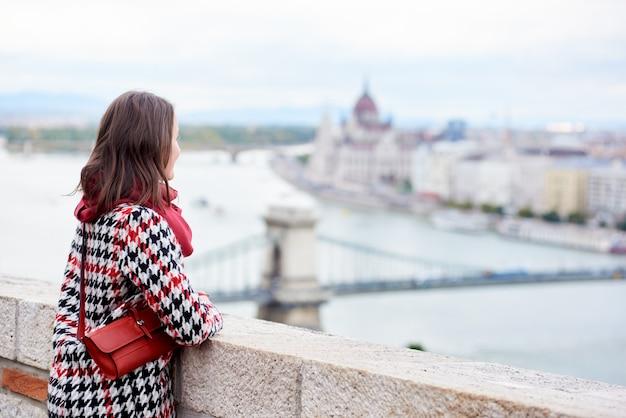 Het donkerbruine meisje geniet van mooi uitzicht van het hongaarse parlement en de kettingbrug in boedapest