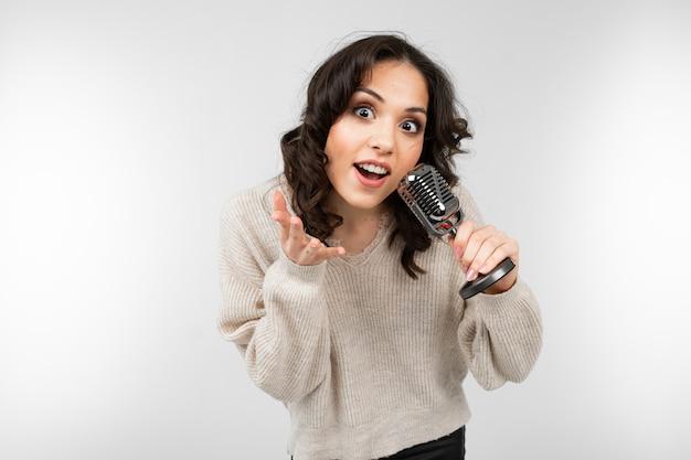 Het donkerbruine meisje in een witte sweater houdt een retro microfoon in haar hand en zingt een lied op een wit