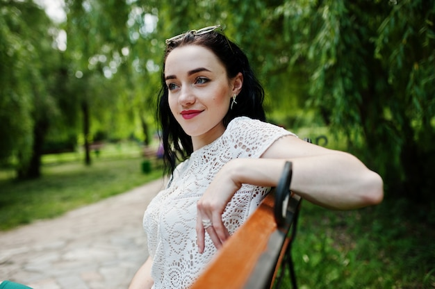 Het donkerbruine meisje in groene rok en witte blouse stelde bij park, zittend op bank.