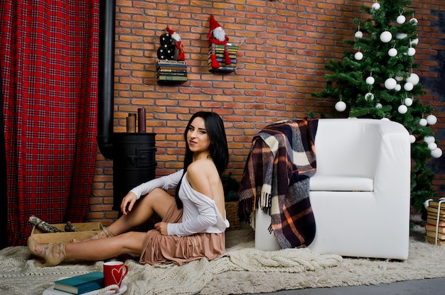 Het donkerbruine meisje in kleding stelde dichtbij nieuwe jaarboom met kerstmisdecoratie in de ruimte van de baksteenstudio.