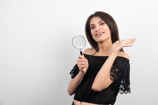 Het donkerbruine vrouw stellen met vergrootglas.