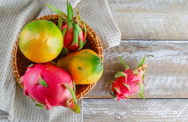 Het draakfruit in een rieten mandvlakte lag op houten en keukenhanddoek