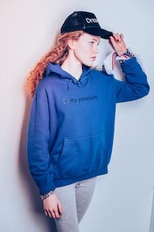 Het dragen van blauwe hoodie. fit tienermeisje met rood krullend haar, gekleed in een blauwe hoodie met tekst erop printed