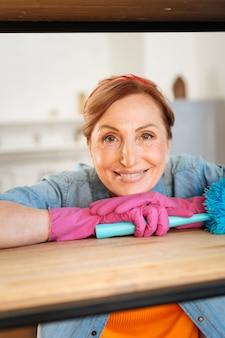 Het dragen van blauwe pluim. vrolijke lichtharige vrouw met bruine ogen die gelukkig is terwijl ze het huis schoonmaakt en haar leven op orde krijgt