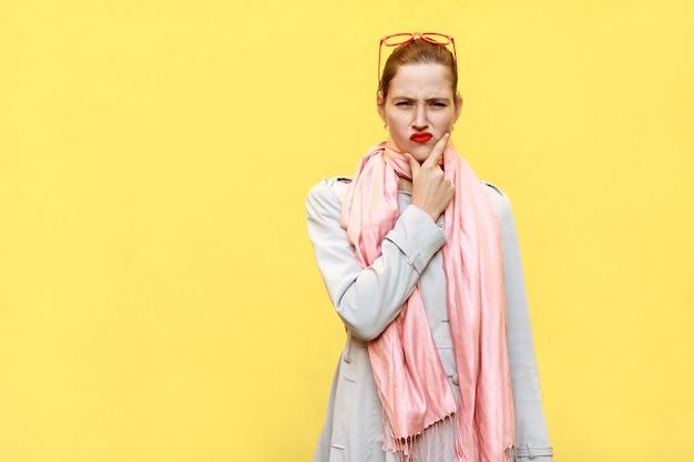 Het dragen van een jas en roze sjaal en denken aan een geïsoleerde studio-opname op gele achtergrond