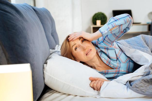 Het dragen van een lichte pyjama. verwarde vrouw die zich slaperig voelt terwijl ze 's morgens vroeg wakker wordt en over haar voorhoofd wrijft