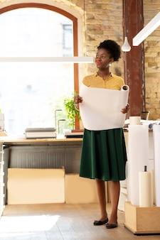 Het dragen van lichte kleding. werknemer van uitgeverij die lichte kleding draagt en papier kiest