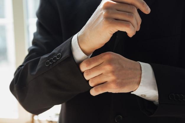 Het dragen van zwarte jas. close up van blanke mannelijke handen, werken op kantoor. concept van zaken, financiën, baan, online winkelen of verkopen. copyspace voor reclame. onderwijs, communicatie freelance.