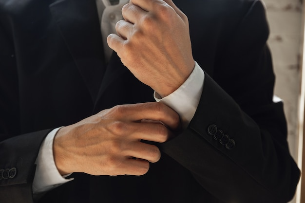 Het dragen van zwarte jas. close up van blanke mannelijke handen, werkzaam in kantoor. concept van zaken, financiën, baan, online winkelen of verkopen. copyspace voor reclame. onderwijs, communicatie freelance.