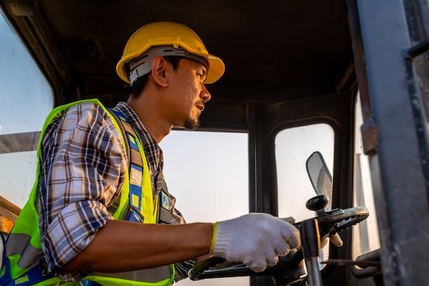 Het drijven van arbeider zware tractor op wielen, wielladergraafwerktuig met backhoe het lossen zandwerken in bouwwerf.