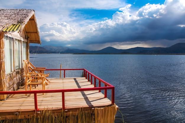 Het drijvende eiland van uros en de traditionele boot van totora op titicaca-meer dichtbij puno-stad, peru