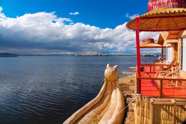 Het drijvende eiland van uros en de traditionele boot van totora op titicacameer dichtbij puno-stad, peru