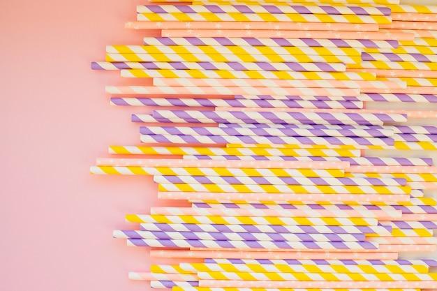 Het drinken van papier kleurrijke rietjes voor zomercocktails op lichte pastel muur met kopie ruimte. eco-vriendelijke herbruikbare rietjes. papieren cocktailbuizen. kraftpapier rietje voor het drinken van koffie of thee