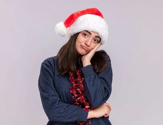 Het droevige jonge kaukasische meisje met santahoed en slinger om hals legt hand op gezicht en kijkt