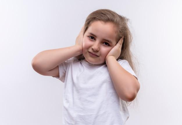 Het droevige kleine schoolmeisje dat wit t-shirt draagt, legde haar handen op de oren op geïsoleerde witte achtergrond