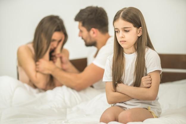 Het droevige meisje dat bij de ouders op het bed zit