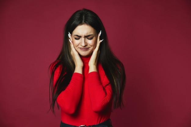 Het droevige mooie donkerbruine kaukasische meisje gekleed in rode trui met irritante hoofdpijn houdt hoofd in handen