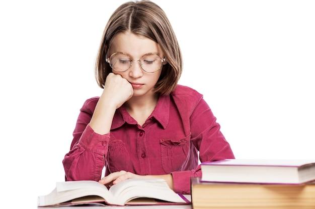 Het droevige tienermeisje in glazen zit aan een lijst met boeken, steunend haar hoofd op haar hand. kennis en onderwijs. .