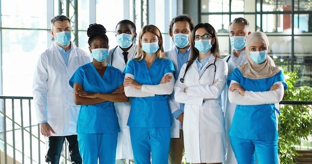Het drukke team van gemengde rassen van mannelijke en vrouwelijke artsen die voor camera stellen en handen kruisen in het ziekenhuis. internationale groep medici in medische maskers. beschermde multi-etnische artsen en verpleegkundigen in kliniek