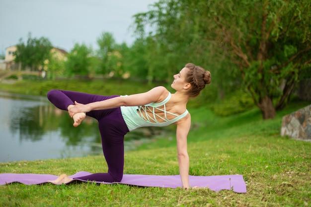 Het dunne donkerbruine meisje speelt sporten en voert mooie en verfijnde yogahoudingen uit in een zomerpark. groen weelderig bos en de rivier op de achtergrond. vrouw die oefeningen op een yogamat doet