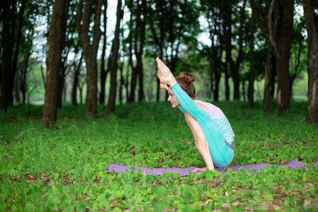 Het dunne donkerbruine meisje speelt sporten en voert mooie en verfijnde yogahoudingen uit in een zomerpark