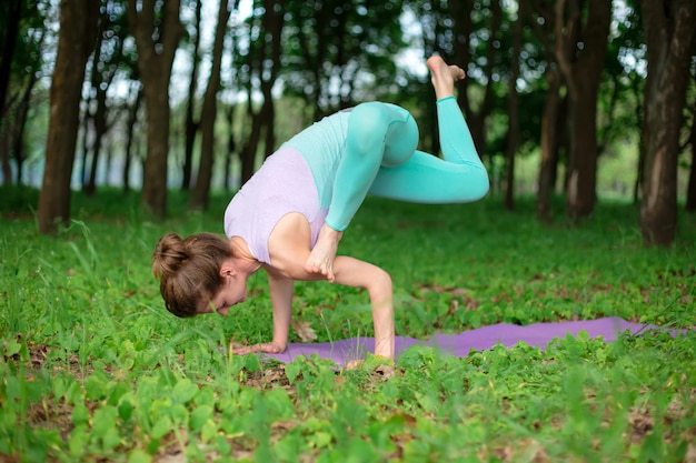Het dunne donkerbruine meisje speelt sporten en voert mooie en verfijnde yogahoudingen uit in een zomerpark.