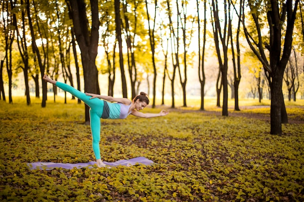 Het dunne donkerbruine meisje speelt sporten en voert yogahoudingen uit in de herfstpark op een zonsondergang. vrouw die oefeningen op de yogamat doet. herfst bos. zachte focus