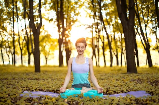 Het dunne donkerbruine meisje speelt sporten en voert yogahoudingen uit in de herfstpark op een zonsondergang