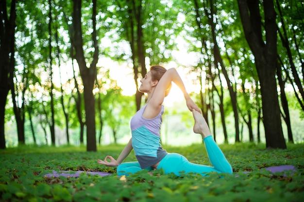 Het dunne donkerbruine meisje speelt sporten en voert yogahoudingen uit in een de zomerpark