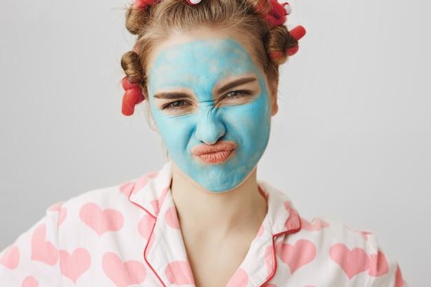 Het dwaze mooie blonde meisje in gezichtsmasker en haarkrulspelden rimpel neus