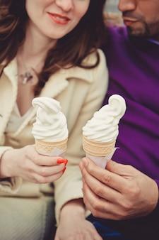 Het echtpaar eet ijs. hij en zij hebben ijs in hun handen.