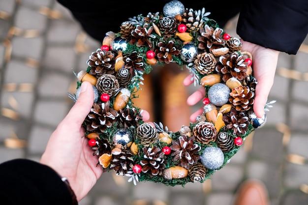 Het echtpaar houdt kleurrijke handgemaakte kerstkrans met kegels en glinsterende ballen in hun handen