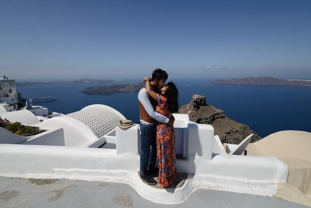 Het echtpaar zit op het dak in santorini, knuffelen en lachen