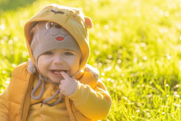 Het eenjarige kind zit op het groene gras en huilt overstuur kleine jongen in grappige hoed en geel