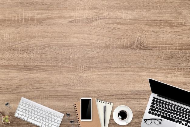 Het eenvoudige houten bureau van de werkruimtetechnologie met laptop computer, koffiekop en exemplaarruimte