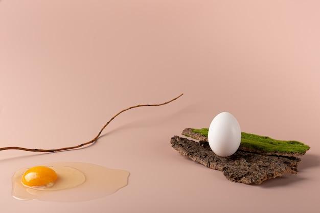 Het ei is gebroken op een delicate roze achtergrond. een heel ei op de bast van een boom. eco-stijl