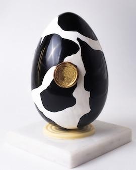 Het ei van de vooraanzichtchocolade bij koe zwart-wit kleuren op tribune