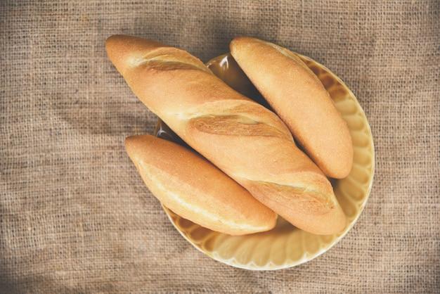 Het eigengemaakte concept van het ontbijtvoedsel / brood en broodjesassortiment verse bakkerij op plaat met zakachtergrond