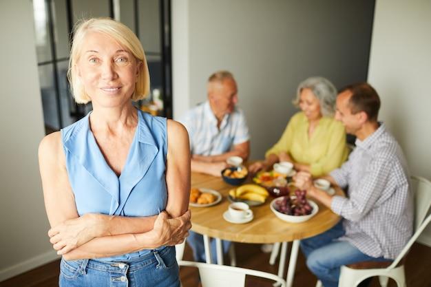 Het eigentijdse rijpe vrouw stellen in keuken