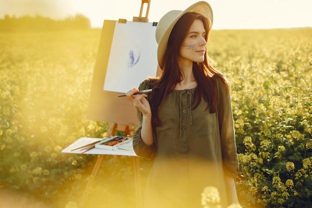 Het elegante en mooie meisje schilderen in een gebied
