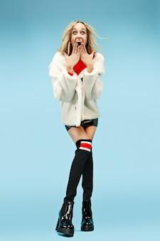 Het elegante jonge vrouw van gemiddelde lengte bij studio. vrouwelijke mode en winkelen concept