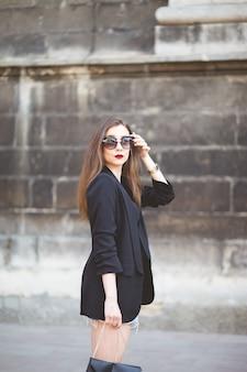 Het elegante meisje in zonnebril loopt rond de stad