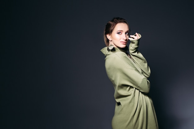 Het elegante zwangere vrouw stellen bij donkere studio.